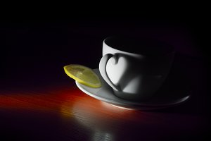 white on saucer cup with lemon in dark