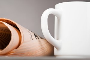 cup and folded newspaper