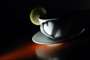 cup with lemon in dark