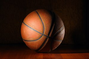 basketball ball in dark on wooden floor