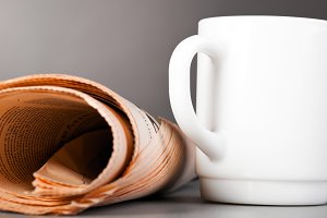 white cup and folded newspaper