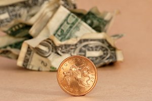 golden coin and crumpled dollar
