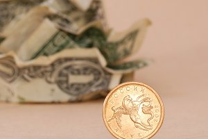 Crumpled dollars and golden coin