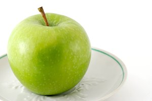 Green apple on a saucer