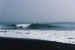 Blue Waves on Black Beach in Fog