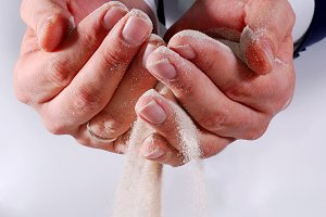 Male business hands trying to hold sand
