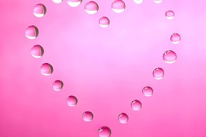 Pink heart shape made of water droplets