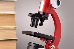 books and microscope, scientific or educational concept