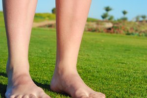 female legs on grass