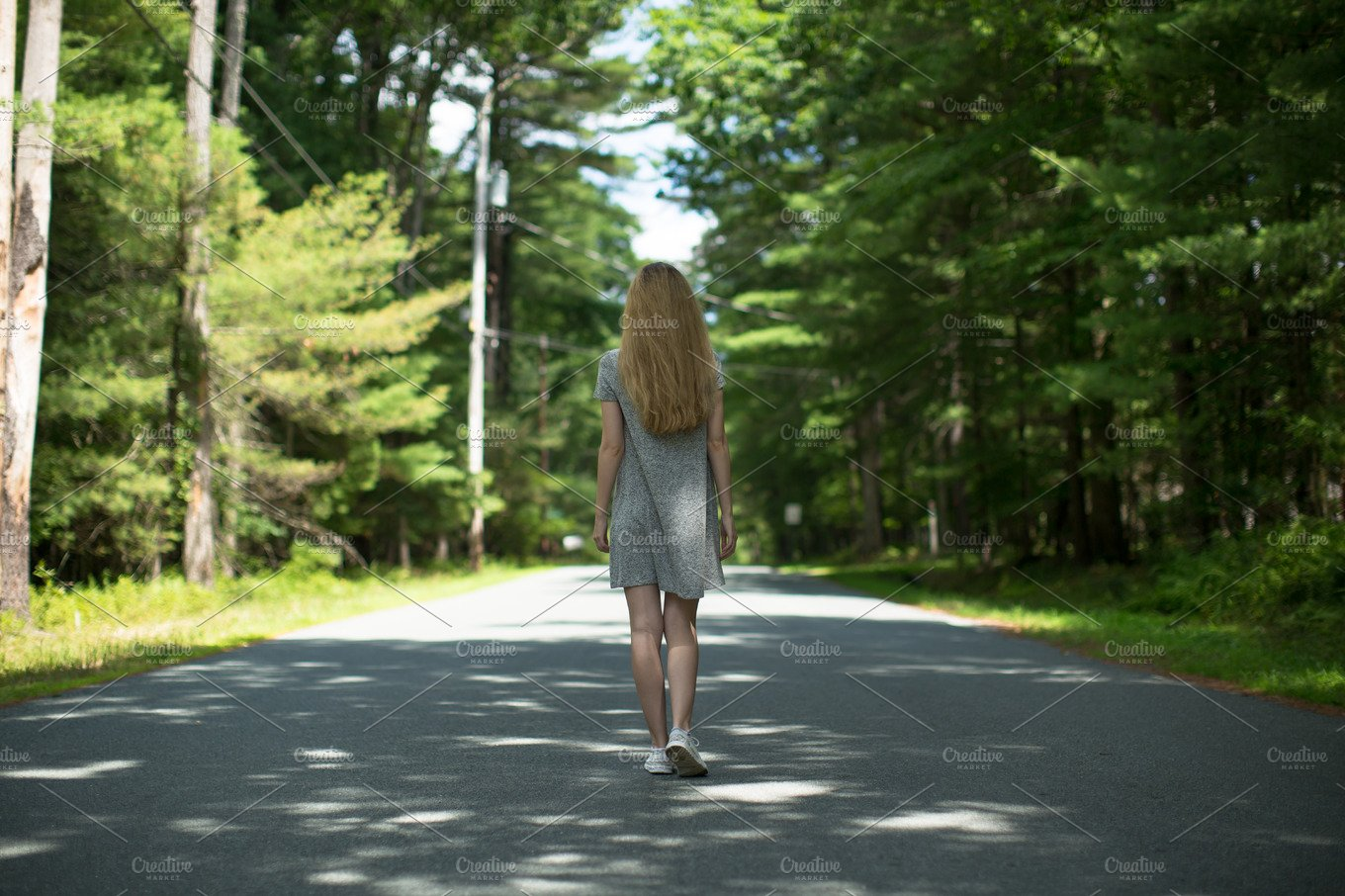 Girl walking down the road in forest ~ People Photos