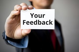 Businessman presenting 'Your Feedback' word on white card