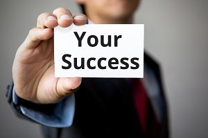Businessman presenting 'Your Success' word on white card