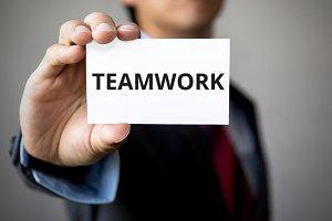 Businessman presenting 'TEAM WORK' word on white card