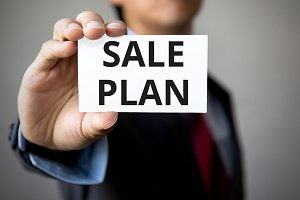 Businessman presenting 'Sale Plan' word on white card