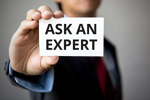 Businessman presenting 'Ask An Expert' word on white card