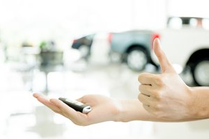 Human hands giving thumbs up with car key in car shoowroom