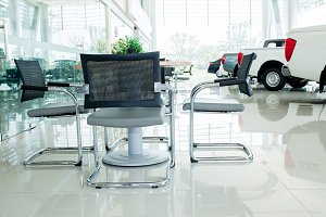 Inside car showroom interior with group of chairs and table for discussion