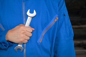 Man in blue technician uniform holding a wrench