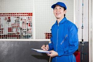 Asian car technician smiling in garage service