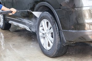 People cleaning and washing car with high pressure washer (focus on car tire)