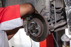 Young technician fixing brake disk in car garage