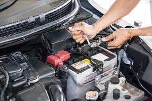 Mechanic engineer fixing car battery in garage (selective focus)