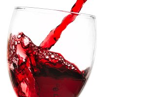 Red wine flowing from a green bottle to a glass. All is isolated with a clipping path