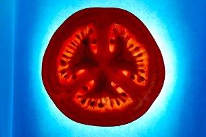 illuminated tomato slice on blue paper background