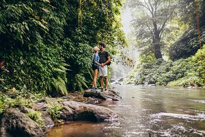 Couple kissing in forest creek