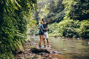 Hiking couple by stream looking