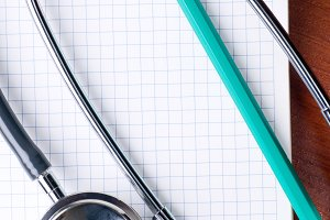 stethoscope with pen on a notepad