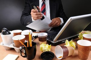 Businessman Stapling Papers at Messy