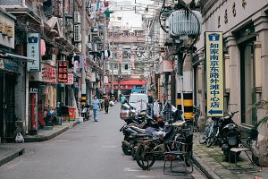 Old narrow Shangkhai street with old bykes and thousands of wires between buildings