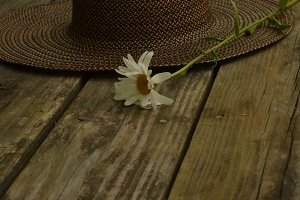 Straw Hat and Daisy on Outdoor Table