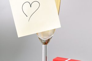 champagne glass with heart on sticky note, red gift box and cork