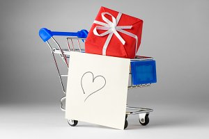 closeup of a shopping cart with gifts and heart