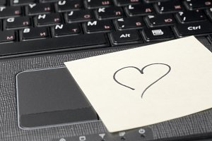 heart on sticky note on computer keyboard