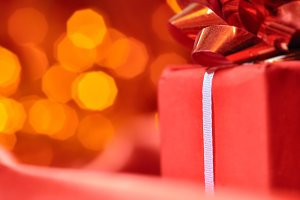 closeup of a red gift box with blurred lights on background