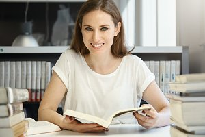 Cute undergraduate student girl wearing white T-shirt, sitting at the desk, reading a book, preparing for a lesson, looking at the camera with happy cheerful expression. People and education concept