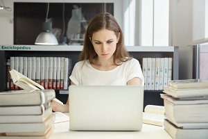 Portrait of female student sitting at the bookshelf and using laptop in the library, reading books, writing thesis with serious face expression. Young Caucasian woman working on her home assignment