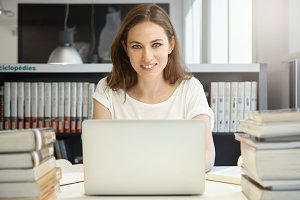 People and education. Attractive Caucasian woman teacher smiling at the camera, looking happy and cheerful, typing on keyboard of her laptop with copy space for your text or promotional content