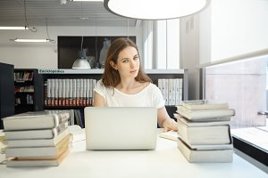 Romantic-looking Caucasian University girl, studying in the library, using laptop, reading books, isolated against background of bookshelves, looking at the camera with sly look, dressed casually