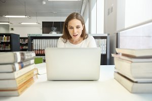 Close up portrait of pretty young college girl, looking with surprise at the laptop with copy space for your promotional information, surrounded by books and bookshelves. People and education