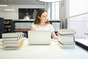 Portrait of young female geography teacher working on her lecture, using laptop computer with blank copy space for your advertisement, searching information in books, sitting at college library
