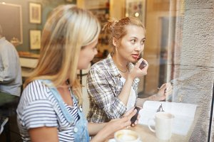 Two young women sitting in a cafÈ with coffee near the window. Blond girl in checked shirt and bun of hair rouging her lips and looking at reflection in the glass. How to do casual makeup concept.