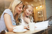 Two young blond girls reading fashion magazine in comfy coffee shop near the window. Nice woman with long hair smiling and the other girl with bun in checked shirt looking at page with pleasure.