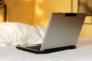 open laptop on a bed