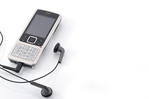 Mobile phone with earphones. Mobile music. Isolated on a white background