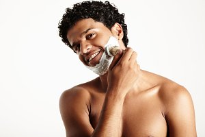 Latin man after shower is shaving