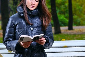 beautiful woman is sitiing in park and reading